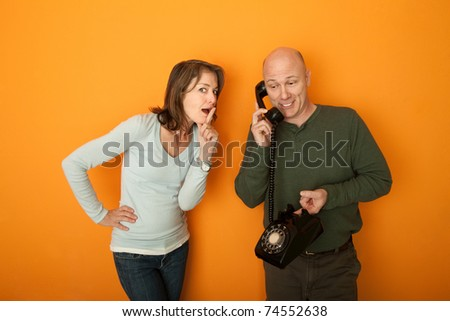 Woman gestures to be silent while man is on telephone conversation - stock photo