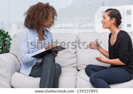 Woman gesturing and speaking to her therapist who is taking notes - stock photo