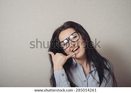 Woman gesturing call me. On a gray background. - stock photo