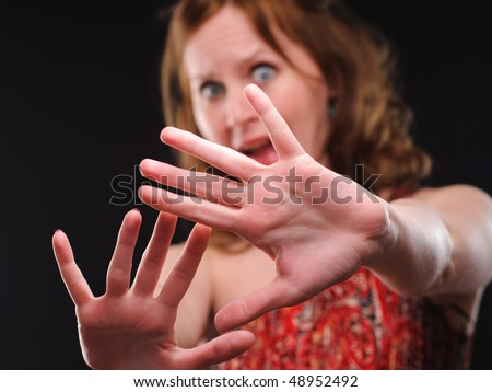 Woman gesturing stop sign. Focus on arm.