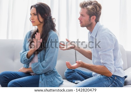 Woman gesturing while quarreling with her partner in the living room - stock photo