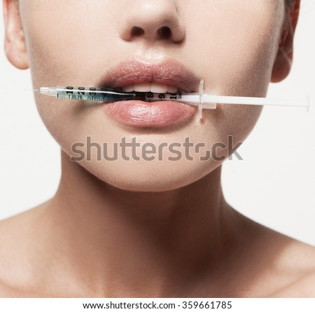 woman gets an injection in her lips. increase the lips by hyaluronic acid - stock photo