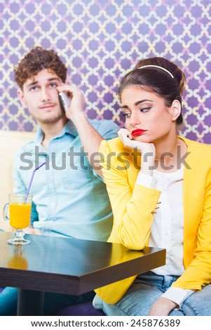 Woman gets bored while her date is talking on the phone  - stock photo