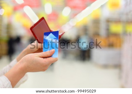 Woman gets credit card from purse in store; shallow depth of field - stock photo