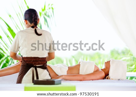 Woman getting a massage on her body at the spa - stock photo