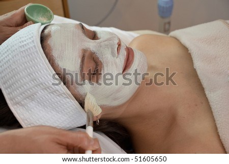 woman getting a white facial mask painted in spa - stock photo