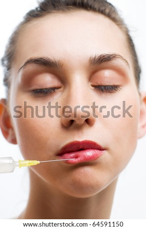 Woman getting an injection or hyaluronic, collagen,HA injection in lips - stock photo