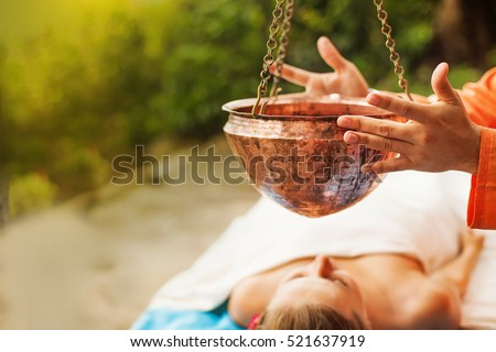 woman getting ayurvedic treatment Shirodara with hot oil pouring on a forehead