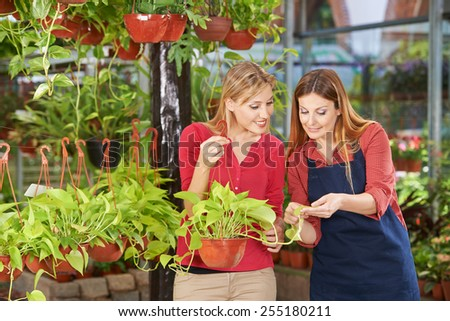 Woman getting competent advice in nursery shop from a gardener - stock photo