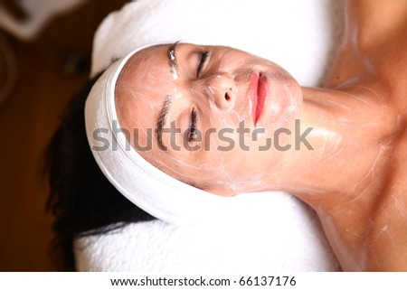 woman getting cream spa lotion on face for beauty treatment - stock photo