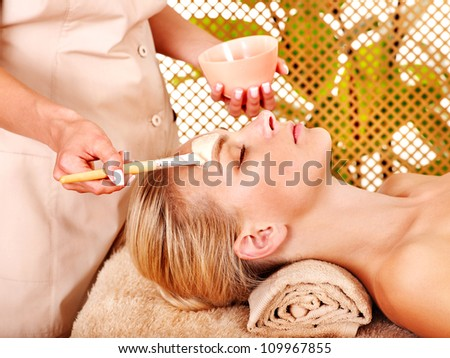 Woman getting facial mask in tropical beauty spa. - stock photo