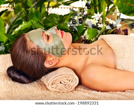 Woman getting facial mask in tropical beauty spa.