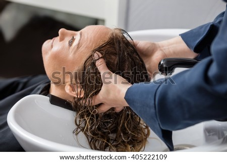 Woman Getting Hair Washed At Salon - stock photo