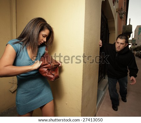 Woman getting her mace to protect herself from the thug who is about to creep around the corner and attack - stock photo