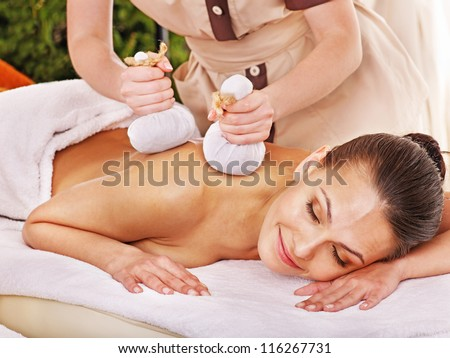 Woman getting herbal ball massage treatments  in spa. - stock photo