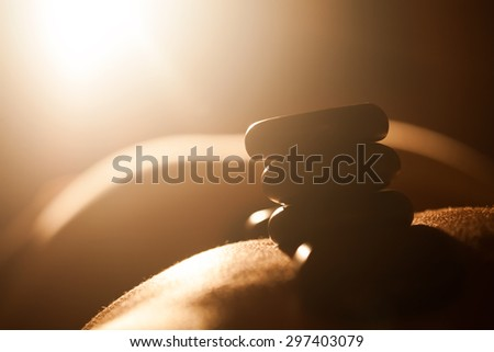Woman getting hot stone therapy against bright sunlight at spa salon. Skin and bodycare - stock photo