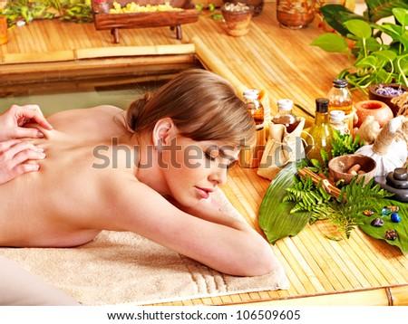 Woman getting massage in spa near water. - stock photo