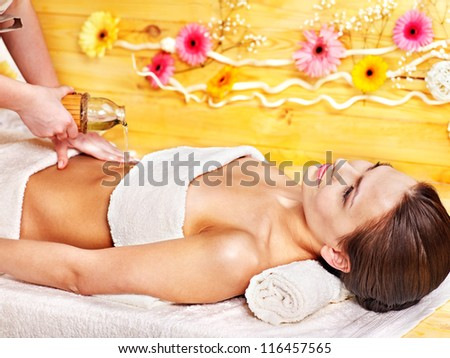 Woman getting  massage in wooden spa. - stock photo