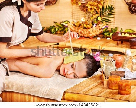 Woman getting massage with ear candle in bamboo spa. - stock photo