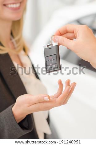 Woman getting modern car key on a car background - stock photo