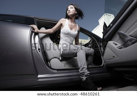 Woman getting out of a car - stock photo