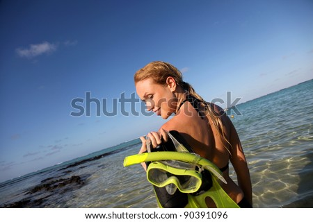 Woman getting out of water after snorkeling journey - stock photo
