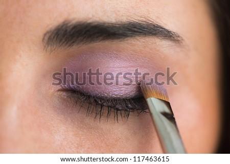 Woman getting purple eye shadow applied - stock photo