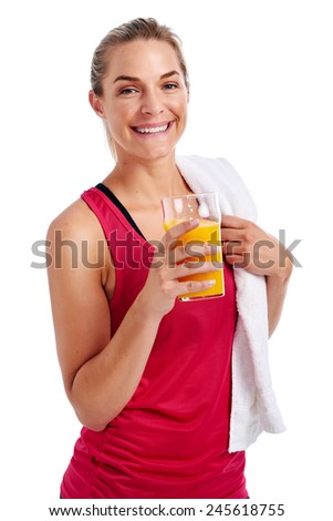 Woman getting ready for gym workout with towel and orange juice in studio