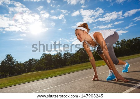 Woman getting ready to start on Stadium - summer outdoors training. - stock photo