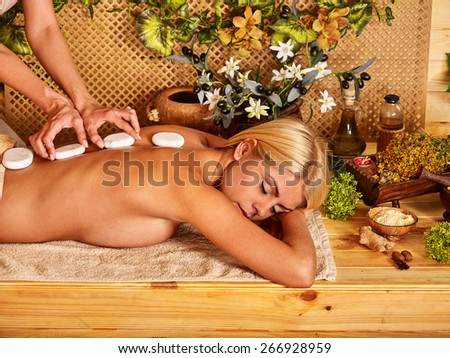 Woman getting relaxing stone therapy massage .Sleeping.