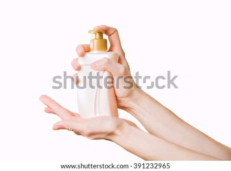 Woman getting soap from a dispencer. Hands with liquid pumping lotion - stock photo