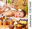 Woman getting thai herbal compress massage in spa. - stock photo