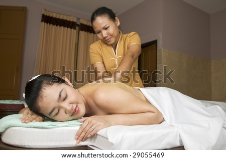 Woman getting Thai massage from professional masseuse