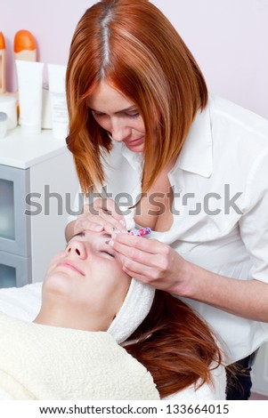 woman getting tweezing eyebrow by beautician