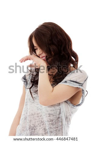Woman giggles covering her mouth with hand - stock photo