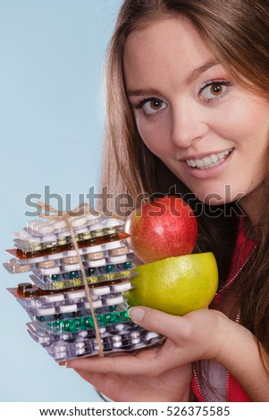 Woman girl holding vitamin tablets pills and fruits. Choice between natural and synthetic vitamins. Health care. Healthy lifestyle nutrition concept.