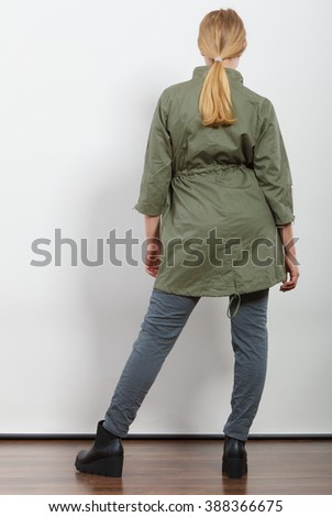 Woman girl in dark green khaki coat and winter boots posing in studio. Autumn fall fashion. - stock photo