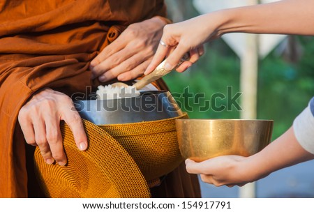 Woman give alms to a Buddhist monk on morning - stock photo
