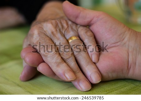 Woman gives grandma her hand - stock photo