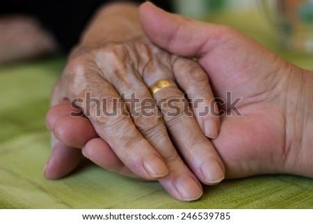 Woman gives grandma her hand - stock photo