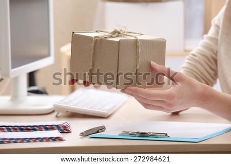 Woman gives parcel in post office - stock photo