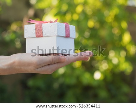 Woman giving a gift box  on bokeh background.