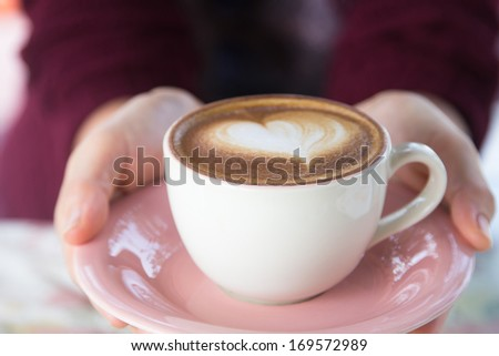 woman giving a hot cup of coffee, with heart shaped froth art - stock photo