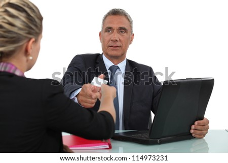 Woman giving a man her businesscard - stock photo