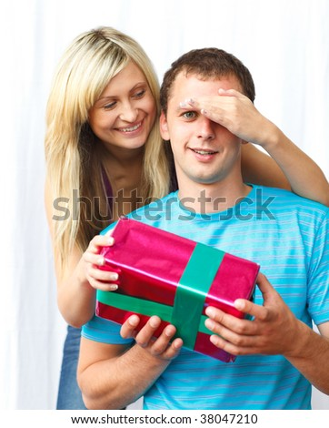Woman giving a present to her boyfriend and covering his eyes with her hand