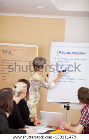 Woman giving a presentation on a flipchart to a group of young business students - stock photo