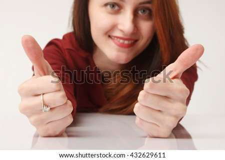 woman giving a thumbs up (gestures, body language, psychology) - stock photo
