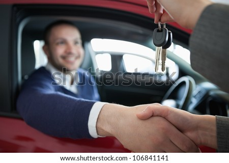Woman giving car keys while shaking hand in a dealership - stock photo