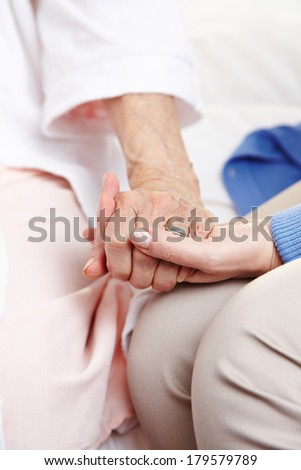 Woman giving condolence to senior citizen woman after death of her husband - stock photo