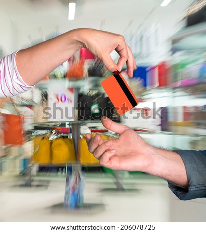 Woman giving credit card to man at shopping mall - stock photo